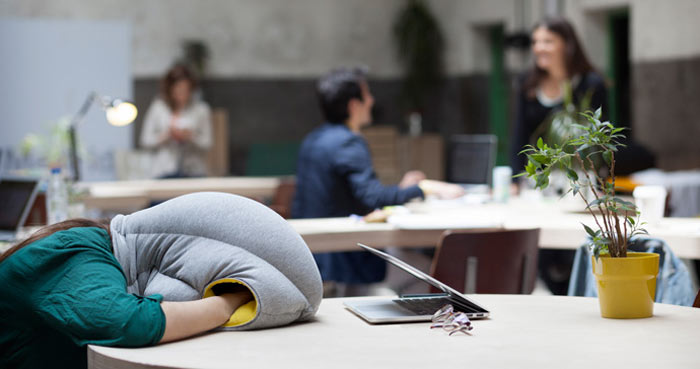 Women using the Ostrich Pillow to take a nap on a table