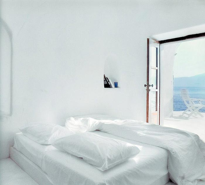Bedroom with white walls and beddings at Perivolas Hideaway in Thirassia, Santorini