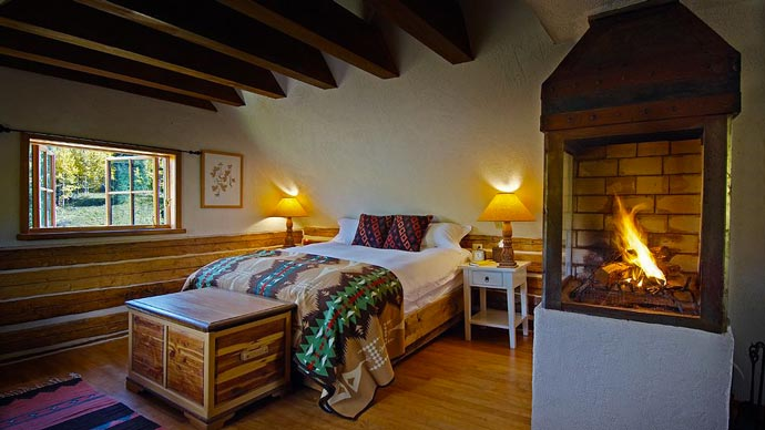 Bedroom design with a fireplace at Duntion Hot Springs in Colorado