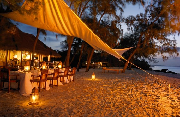 Beach restaurant at night at Vamizi Island Lodge