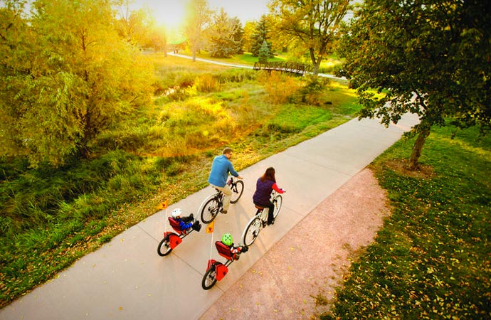 Parents riding bicycle trailers