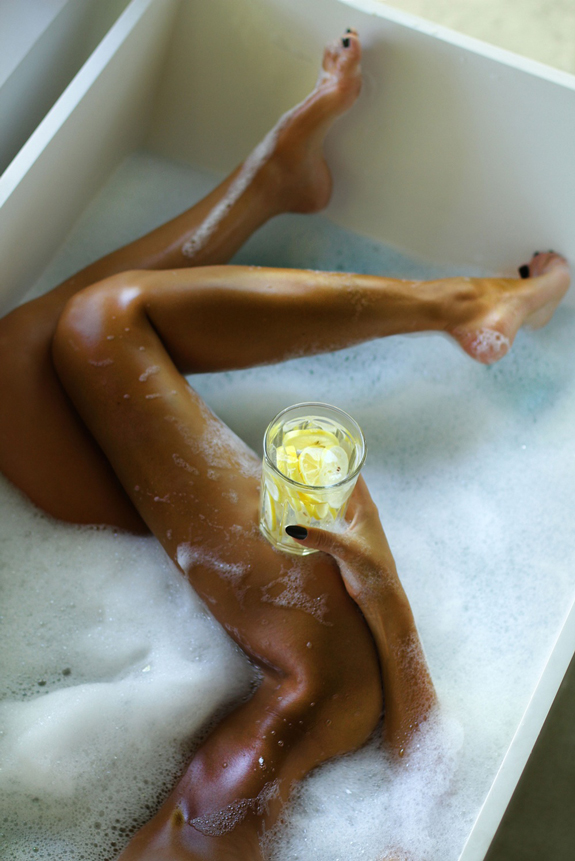 Naked girl's body in a bathtub foam with lemonade in her hands