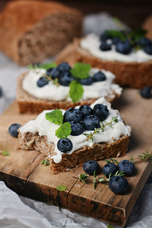 Blueberry and cream sandwich on a wooden cutting board