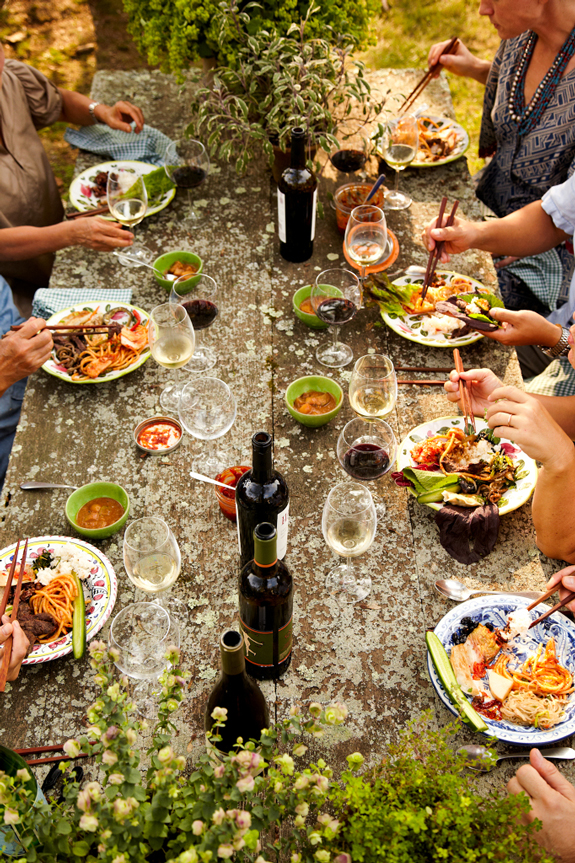 Colorful rustic outdoor dinning table with friends having a lunch