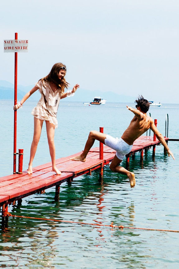 Girl pushes a guy into water from a boardwalk