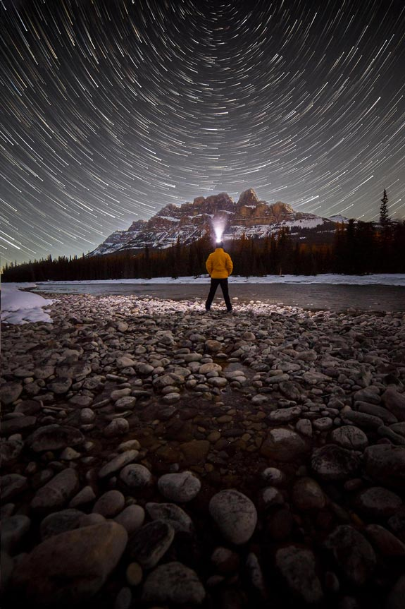 Man at night with head lamp open skies and stars