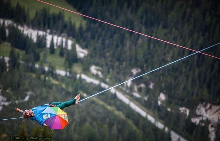 Woman lying down on tight rope at the Slackline Festival