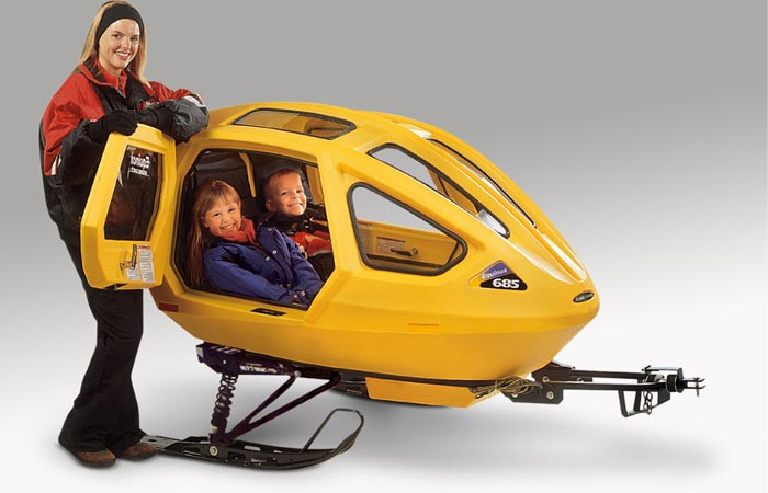 Two children in a Equinox Snowcoach