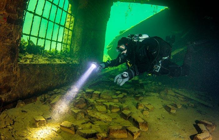 Scuba diver inside Rummu underwater prison
