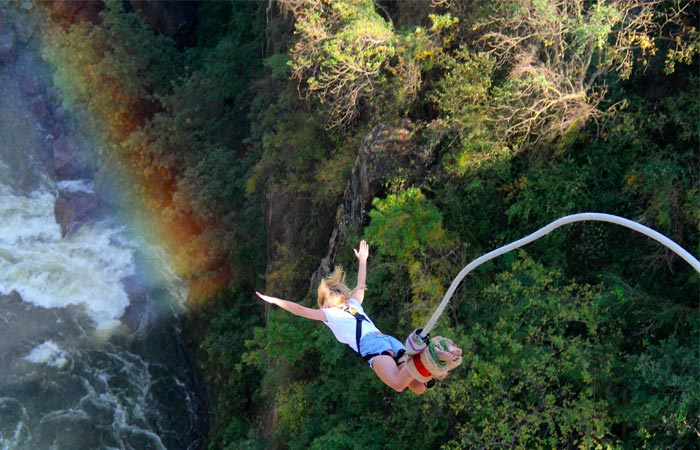 Woman bungee jumping off Victoria Falls