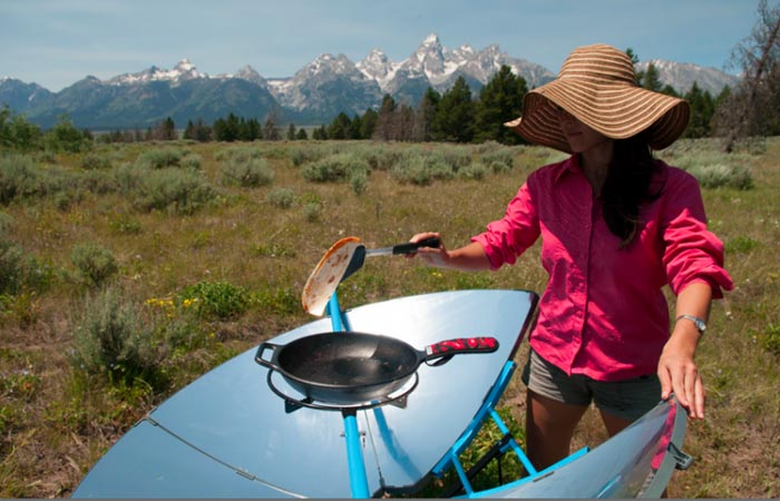 Woman using the Solsource Solar Cooker