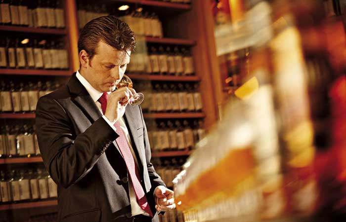 A man in a library drinking whiskey