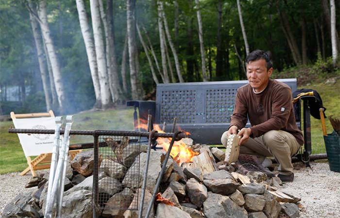 Setsumasa Kobayashi sitting next to a fire pit