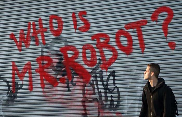 Elliot Alderson next to Who Is Mr Robot graffiti