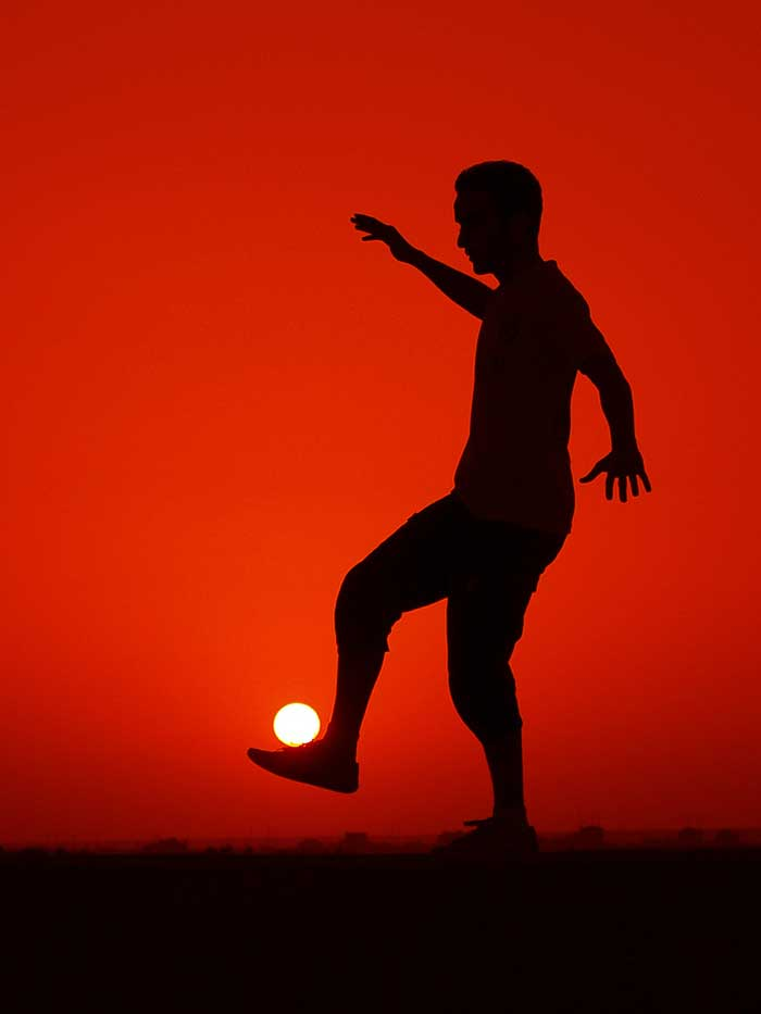 A guy playing soccer with the sun