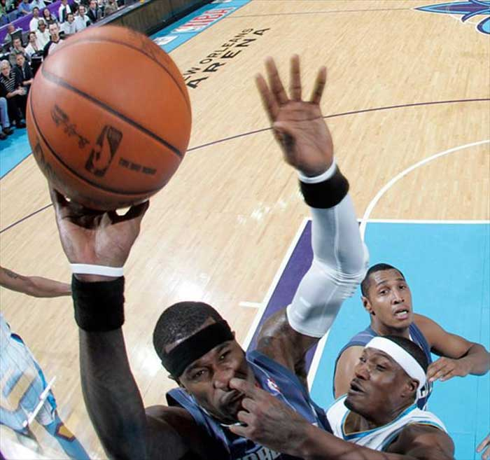 A basketball player picking other basketball player's nose