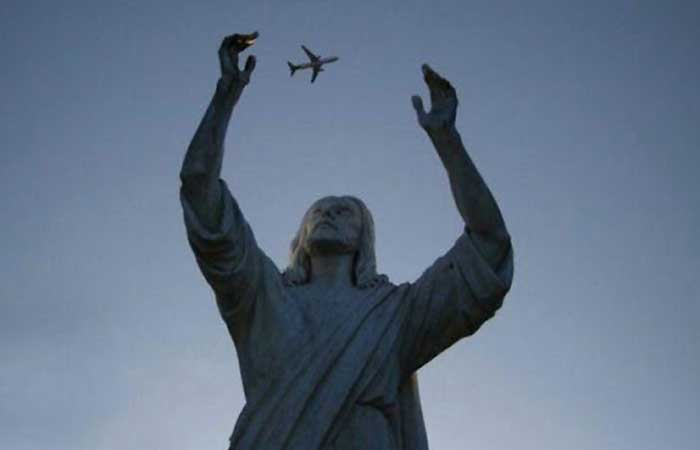 An airplane between monument's hands