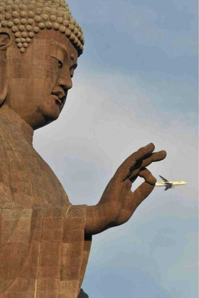 A plane flying next to a monument's hand