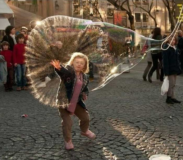 A boy puncturing a bubble balloon