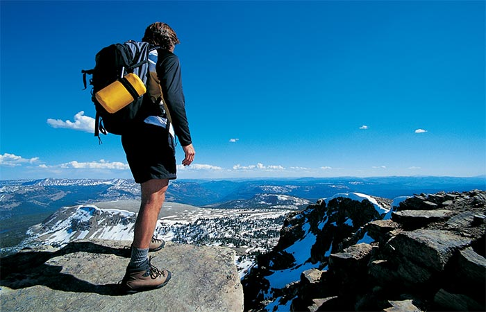 A guy backpacking, standing at a cliff