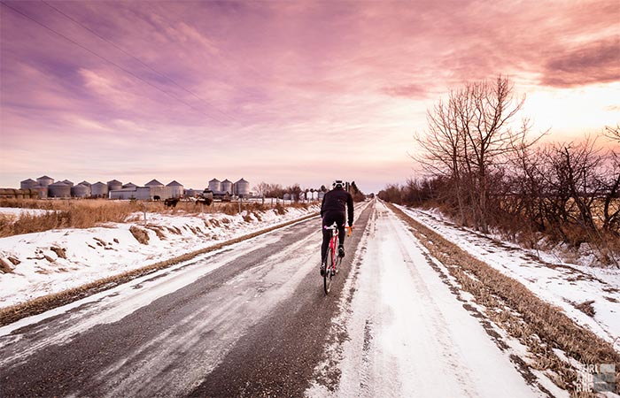 A Guy Riding A Bike In Winter