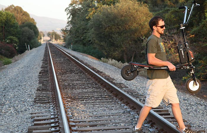 A guy carrying Freedom Electric Stand Up Trikke