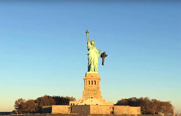 A guy flying next to the Statue of Liberty with JB-9 Personal Jetpack