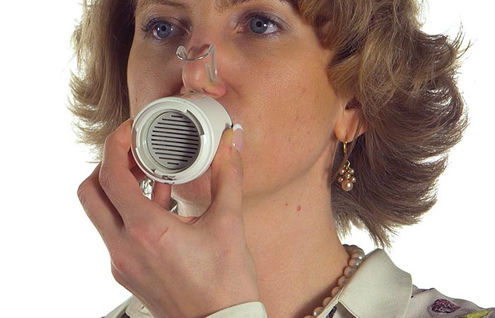 A woman using Saver Emergency Breath System