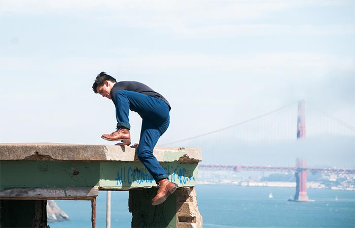 A guy climbing a concrete wall wearing The Venture Pant