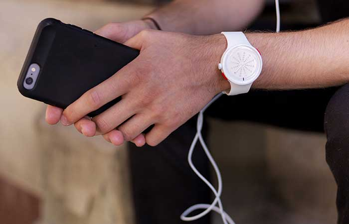 A man holding What watch and an iPhone