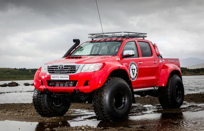 Hilux AT44 6×6 Arctic Truck, red, in wet terrain.