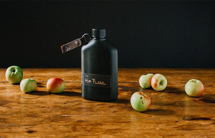 Black Bush Smarts Hip Flask On A Wooden Table With Apples Around It