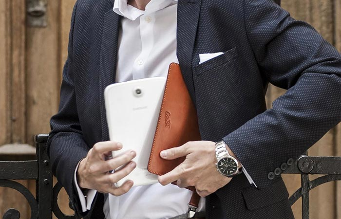 A man in a suit carrying a Carter Shoulder Holster and pulling a white tablet out of it.