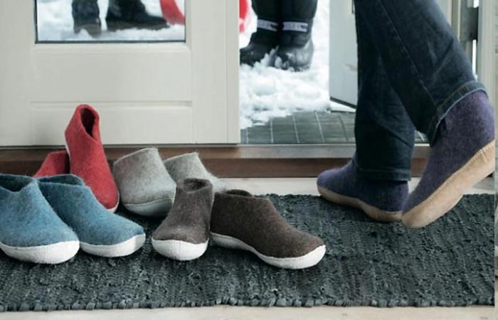 Glerups shoes in different colors piled up at the door step, and a person wearing a pair exiting through the door.