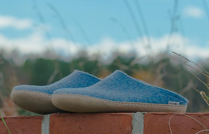 Glerups slip ons, blue, outdoor, on a brick wall.