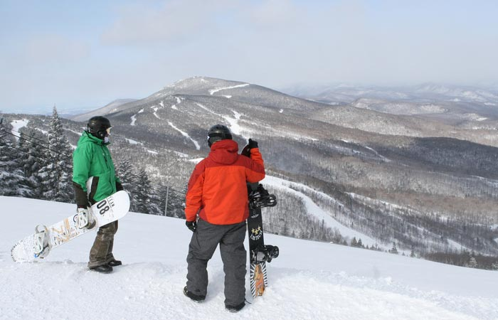 Two snowboarders in Killington ski resort, observing the mountain and runs.