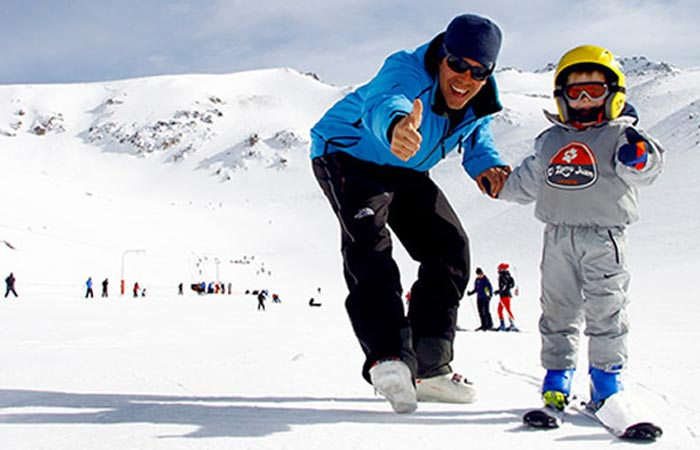Skiing instructor with a child in La Hoya, Argentina.