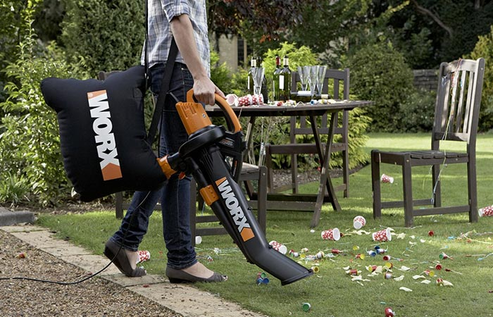 Man cleaning after party with WORX WG509 Electric TriVac BlowerMulcherVacuum