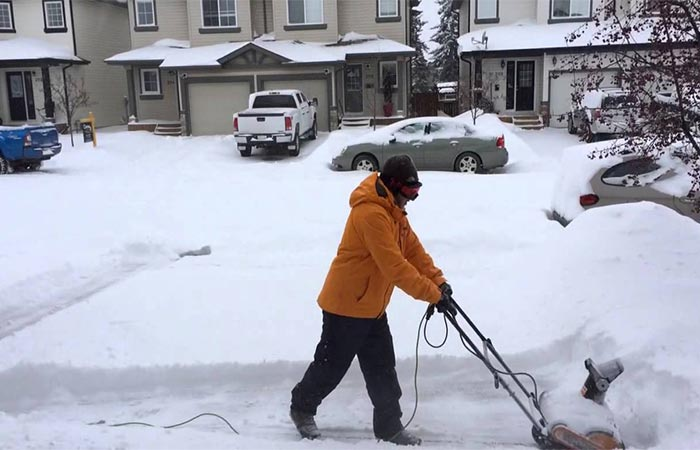 A guy using Worx Electric Snow Thrower