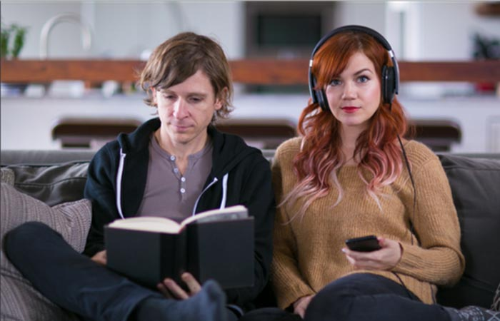 A man reading a book and a woman watching TV using Blipcat sitting on a couch.