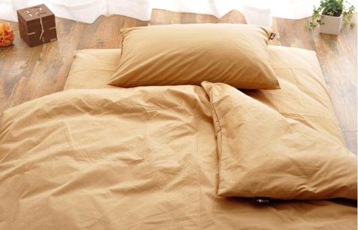 Japanese Futon Mattress And Sheets Bed Withe Beige On A Wooden Floor