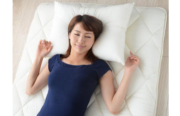 A woman lying on white Japanese Futon Mattress and Sheets on the floor.