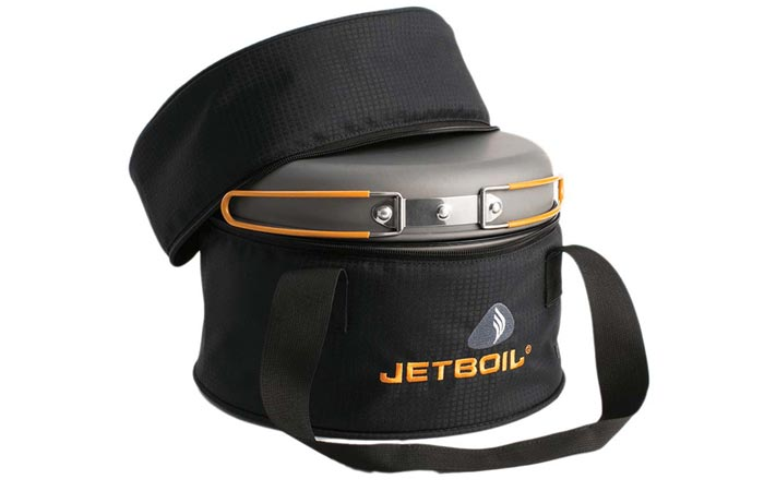 Jetboil Genesis Base Camp Stove, packed in a slightly open black carry bag, on a white background.