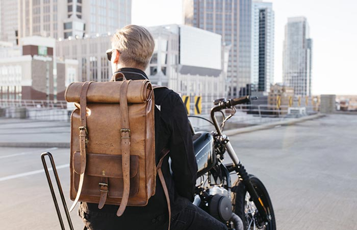 A man on a motorbike on a city street with a Leather Rolltop Backpack by Johnny Fly Co. on his back, rear view.