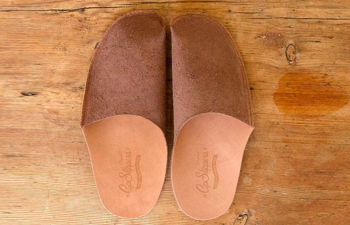 Luxurious Leather Slippers, brown, on a wooden surface.