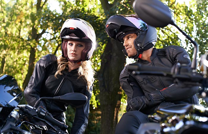 A man and a woman siting on their bikes with helmets on.