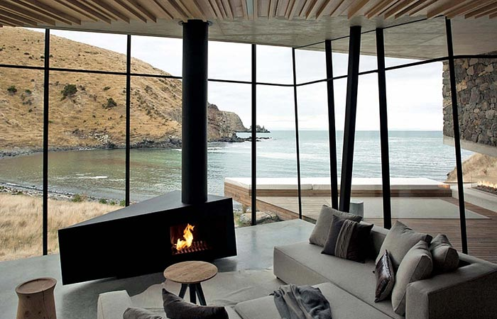 Seascape Retreat on a South Pacific Cove, interior, living room with a sofa and a fireplace, with a beach view.