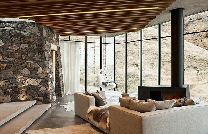 Seascape Retreat on a South Pacific Cove, living room with a sofa and a view at the rocky hills.