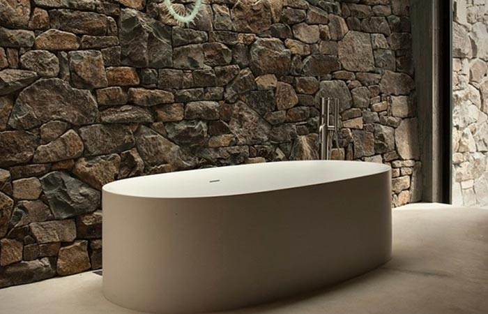Seascape Retreat on a South Pacific Cove, the tub, covered, in front of a rocky wall, with an open door further.