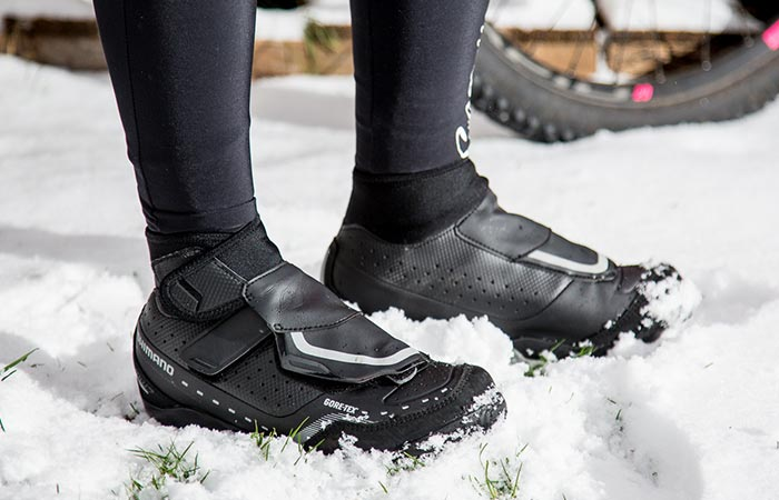 A person wearing bike shoes and walking on snow.